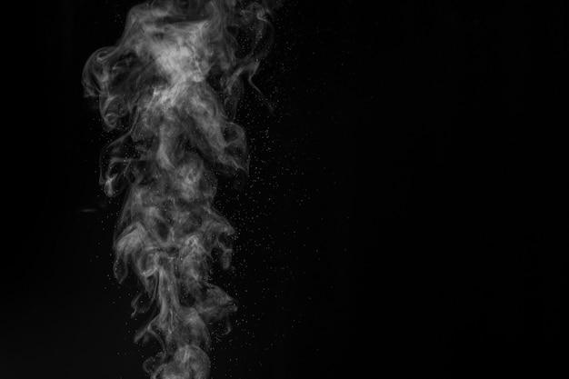 공기 포화 기에서 나오는 흰색 증기 스프레이 증기. 검정색 배경에 연기 조각. 추상적 인 배경, 디자인 요소, 사진 오버레이