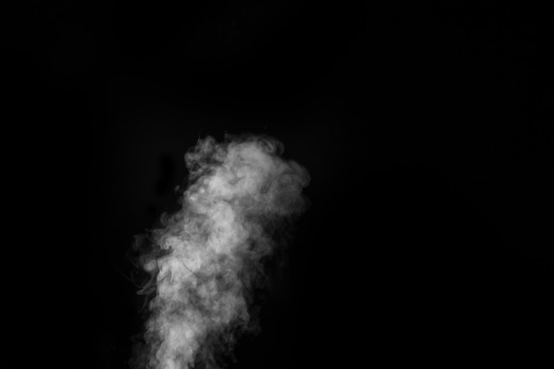 White vapour spray steam from air saturator. smoke fragments on a black wall.