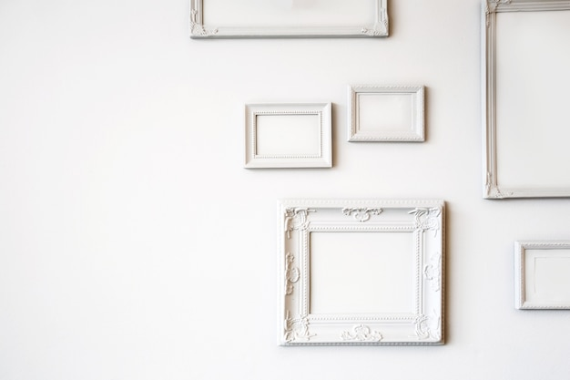 White various antique blank photo or picture frames on the white wall modern design, minimal interior design, copy space or space for text close up