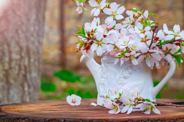 White vase with a bouquet of branches of flowering almonds