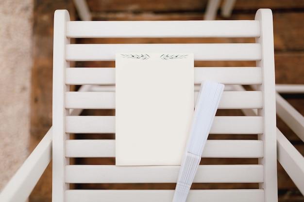 白い縦のシートは、折りたたまれた扇風機の横にある木製の椅子の上にあります