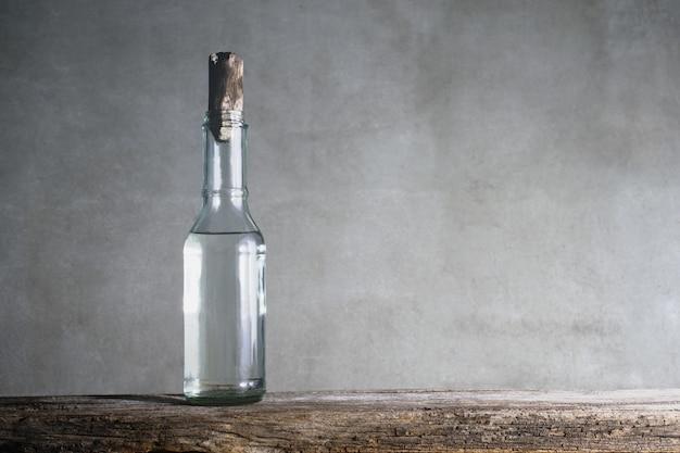 木製のテーブルの上に白酢のボトル。