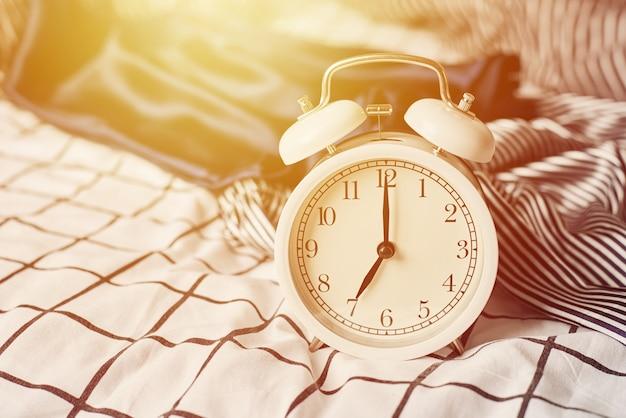 白いビンテージの目覚まし時計とベッドの枕