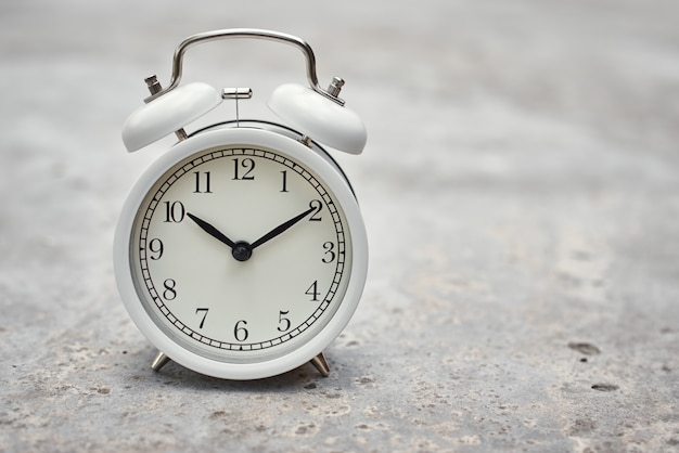 White vintage alarm clock on gray background. productivity control and task planning concept