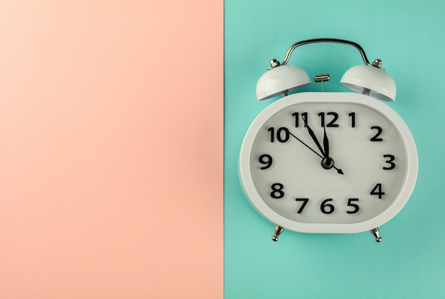 White vintage alarm clock on pink and blue background. - top view.