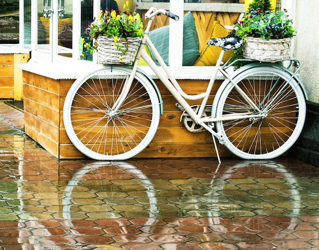 카페 배경 밖에 서 있는 꽃 바구니가 있는 흰색 빈티지 자전거. 아름다운 꽃과 함께 레트로 스타일의 운송