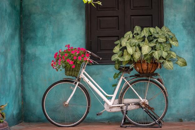 Белый старинный велосипед с корзиной, полной цветов, рядом со старым зданием в дананге, вьетнам