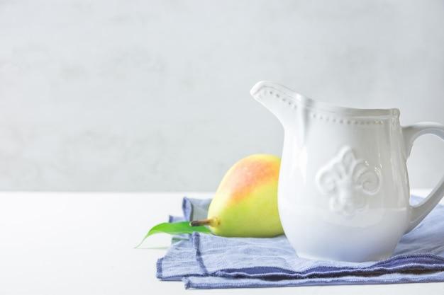 White vintage ceramic milk jug on folded blue linen napkin pear on white table.