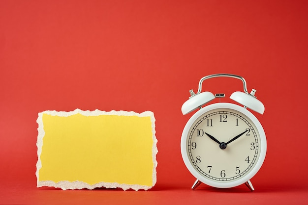 White vintage classic alarm clock with bells and empty torn paper sheet on red background.  design blank for time concept