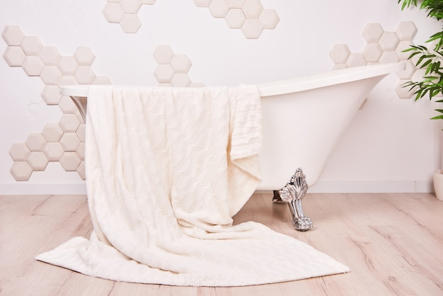 White vintage clawfoot bath in bathroom interior