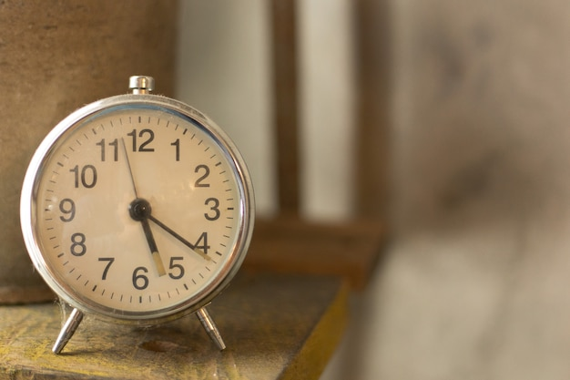 White vintage clock alarm  near window light.