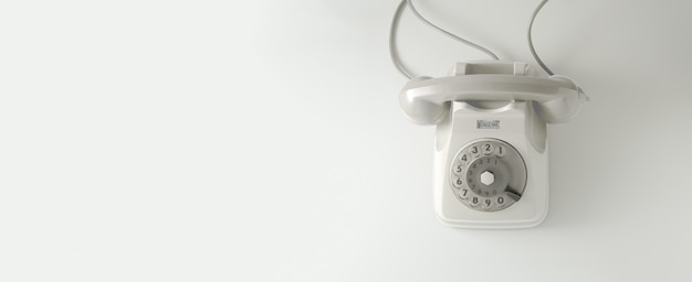 A white vintage dial telephone with white background.