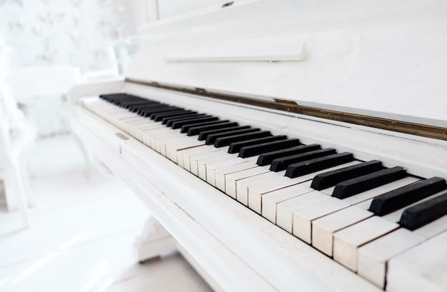 Белое старинное пианино в белой комнате