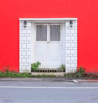 White vintage retro wooden door on red wall background. home interior architecture concept