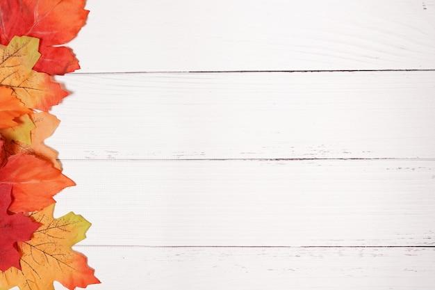가을 노란색과 빨간색 잎이 있는 흰색 빈티지 소박한 나무 배경, 복사 공간