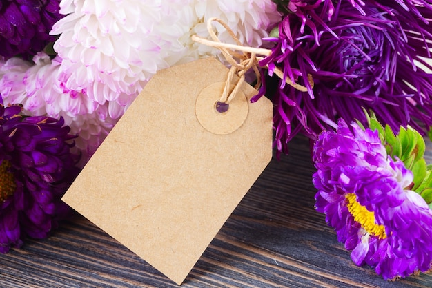 White and violet aster flowers on table with empty paper note