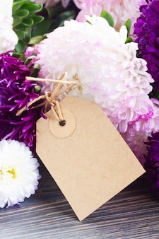 White and violet aster flowers on table with empty paper tag