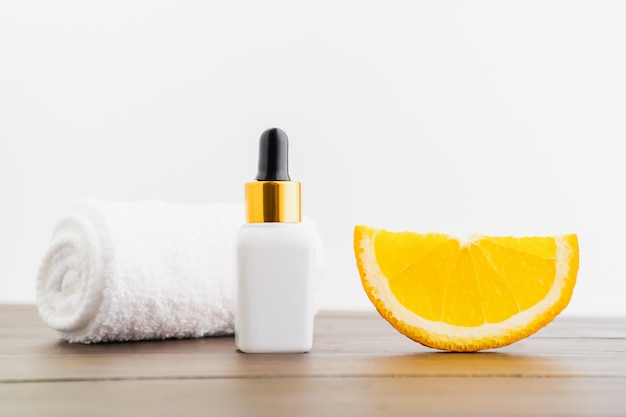 White vitamin c bottle and oil made from orange fruit extract, mockup of beauty product brand. top view on the wood background.