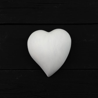White volumetric heart on a black natural wooden background