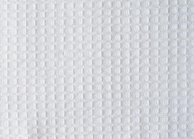 テキスト用の目に見えるテクスチャコピースペースを備えた白いワッフル生地。軽い天然コットンの質感のクローズアップ