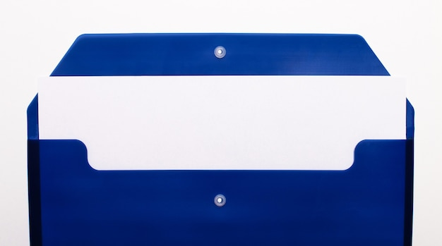 On a white wall, a blue folder for papers with an empty sheet of paper. copy space.