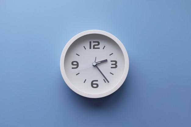 Белые настенные часы на стене. минималистичное плоское изображение пластиковых настенных часов на синем бирюзовом фоне с копией пространства и центральной композицией.