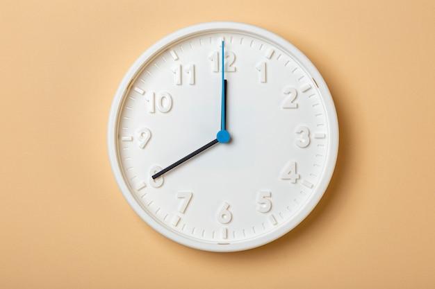 青い秒針が付いている白い壁時計は8時を示しています