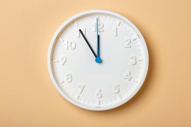 青い秒針が付いている白い壁時計は11時を示しています