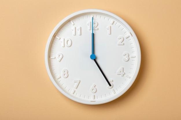 青い秒針が付いている白い壁時計は5時を示しています