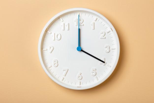 青い秒針が付いている白い壁時計は4時を示しています
