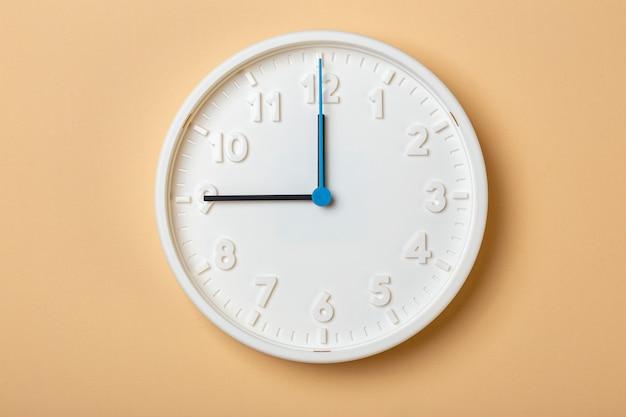 青い秒針が付いている白い壁時計は9時を示しています