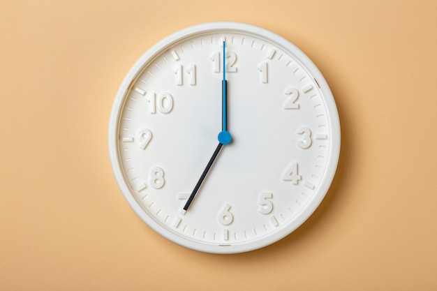青い秒針が付いている白い壁時計は7時を示しています