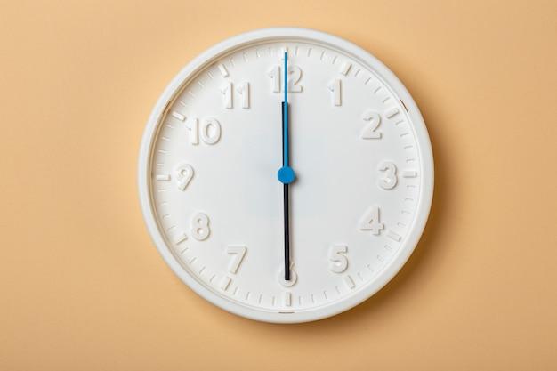 青い秒針が付いている白い壁時計は6時を示しています