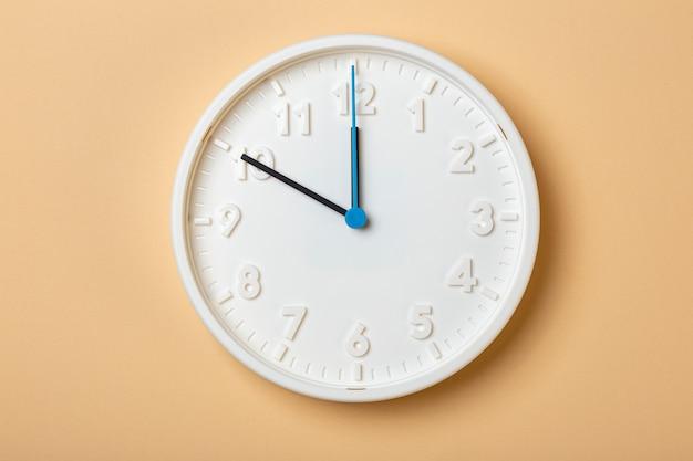青い秒針が付いている白い壁時計は10時を示しています