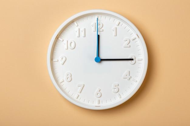 青い秒針が付いている白い壁時計は3時を示しています