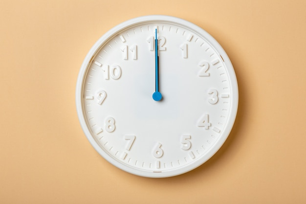 青い秒針が付いている白い壁時計は12時を示しています