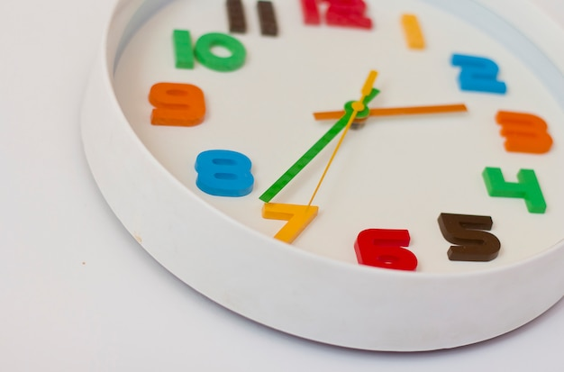White wall clock with color numbers. colored clock for the children's room