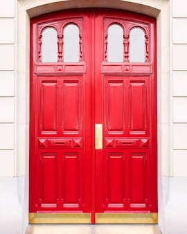 White wall of the house with a closed red wooden door in paris france