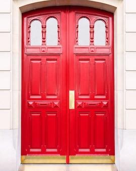 Белая стена дома с закрытой красной деревянной дверью в париже, франция