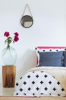 흰색 벽, 둥근 거울, 유리 꽃병 및 무늬 침구