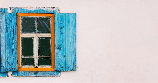 White wall of village house with old wooden window with blue shutters