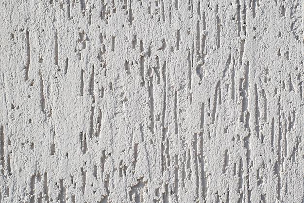 장식용 트림이 있는 흰색 벽. 외부 마감용 퍼티의 질감. 표면에 장식적인 흠집이 있습니다. 공간 배경 복사