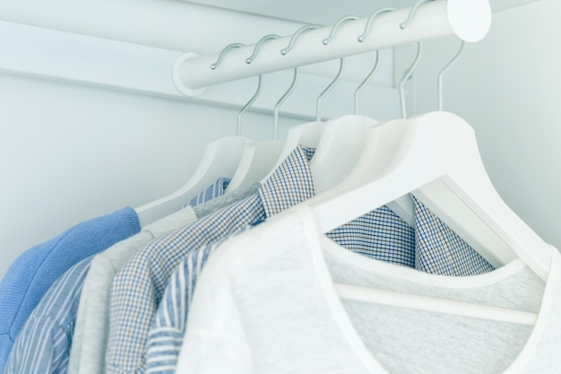 밝은 파란색 셔츠와 블라우스가 옷걸이에 매달려 있는 흰색 옷장. 착색 효과