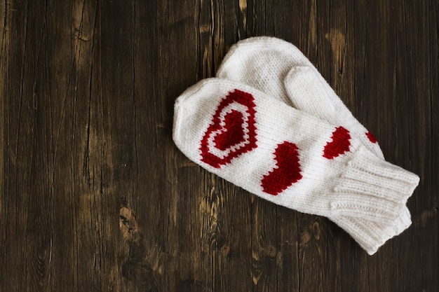 White warm knitted mittens over wooden background