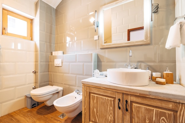 Белый умывальник с большим зеркалом, полотенцесушителем и светодиодной лампой в ванной рядом с унитазом и биде
