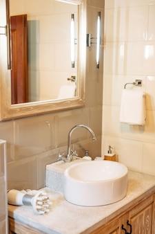 大きな鏡付きの白い洗面台、タオルホルダー、バスルームのledランプ、白いタイル