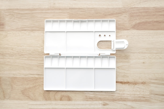 White watercolor palette. empty watercolor tray isolated on wood background. white plastic paint palette.