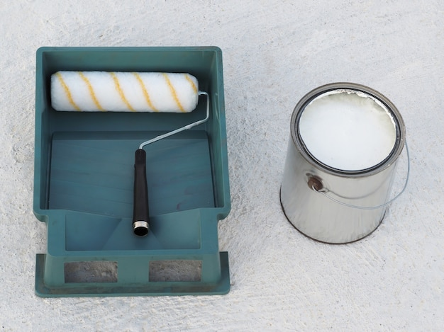 White waterproof paint in bucket with green container and roller at rooftop.
