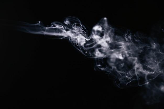 White wavy smoke on black background