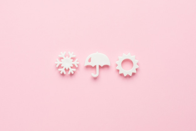 White weather elements in a minimal style on pink, top view.